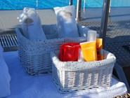 Тапочки и косметические средства для загорающих у бассейна